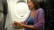 A woman sits on a plane, uses a smartphone and lowers a folding table