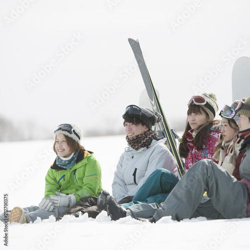 雪原に座り談笑をする若者たち