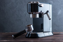 Preparation Of Espresso. Black Coffee Machine And A Horn With Ground Grains On The Table. Professional Coffee Brewing