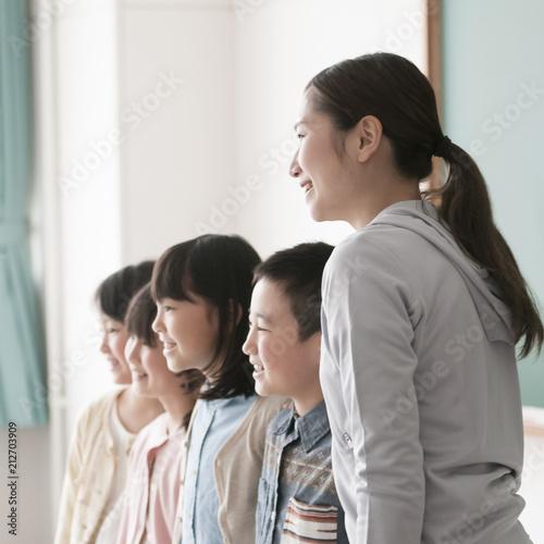 黒板の前に並ぶ小学生と先生