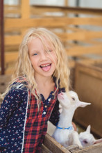 Kid Sticking Tongue Out And Hugging Goat At Farm