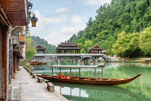 Photo sur Aluminium Olive Parked wooden tourist boat on the Tuojiang River, Fenghuang