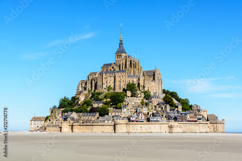General view of the Mont Saint-Michel tidal island, located in France on the limit between Normandy and Brittany, with the exposed sand of the bay at low tide in the foreground under a blue sky Canvas Print