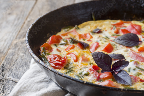 Omelet with vegetables in a pan close-up. Wooden background, top view horizontal