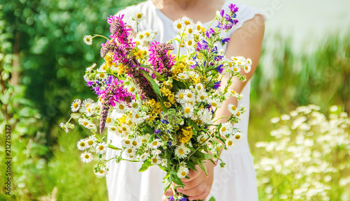 Fotografía  Child with a bouquet of wildflowers. Selective focus.
