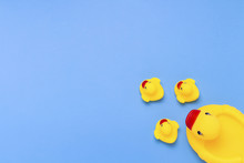 Rubber Toy Of Yellow Color Mama-duck And Small Ducklings On A Blue Background. The Concept Of Maternal Care And Love For Children, The Upbringing And Education Of Children. Flat Lay, Top View