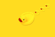 Rubber Toy Of Yellow Color Mama Duck And Small Ducklings On A Yellow Background. The Concept Of Maternal Care And Love For Children. Flat Lay, Top View