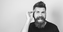 Beauty Portrait Of A Young Funny Man With Beard Like Girl Plucking Eyebrows With Tweezers Isolated Over Gray Background. Young Handsome Bearded Man With Tweezers In His Hands. Black And White