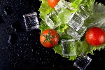 FototapetaBanch of red cherry tomatos, green salad and ice cubes on black wet table. Selective focus