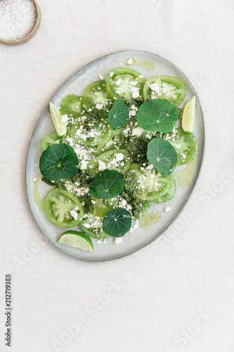 Poster Eten Green hues summer salad with green tomatoes, fresh feta cheese, pesto, lime and nasturtium or East Indian cherrie leafs all presented on an oval ceramic plate seen from above.