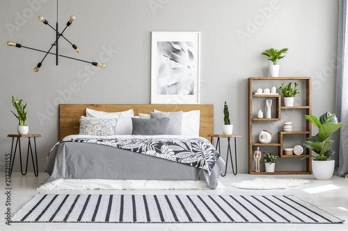 Fototapeta Striped carpet near bed with patterned blanket in bedroom interior with poster and plants. Real photo obraz