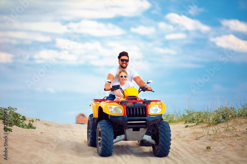 happy family, father and son riding on atv quad bike at sandy beach