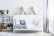 Teddy bear and plants on shelves next to kid's bed in scandi bedroom interior with triangles. Real photo