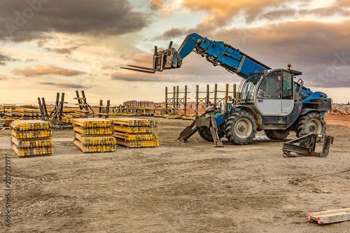 Photo Forklift on a construction site, preparing to raise construction parts
