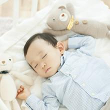 ベビーベッドで眠る男の子