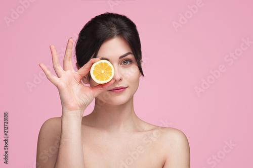 Fototapeta Woman with orange slice in studio