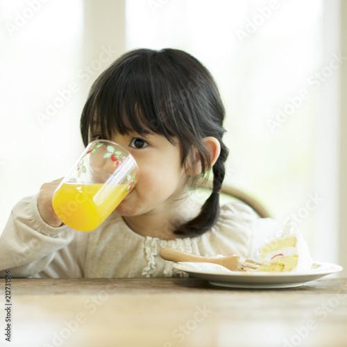 オレンジジュースを飲む女の子