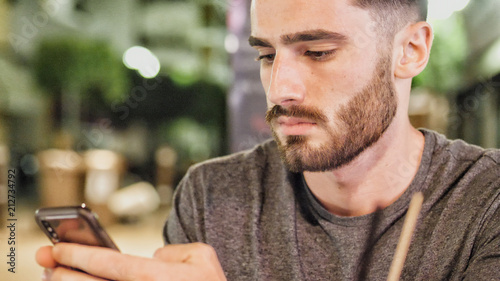Young handsome man outside at night sitting at bar table in a summer day in city Tablou Canvas