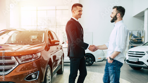 The manager in the dealership shakes hands with a young man in a light shirt against a new car.