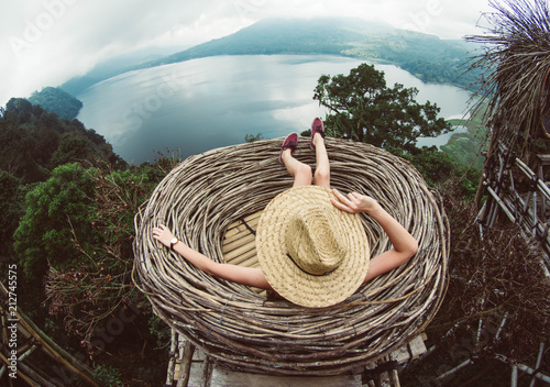 Fotografia  Back view of a young woman in straw hat relaxing looking the landscape