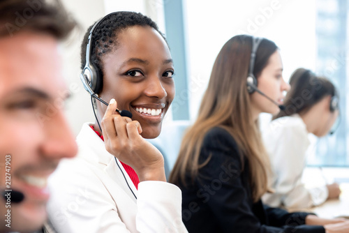 Fototapeta Smiling beautiful African American woman working in call center with diverse team obraz