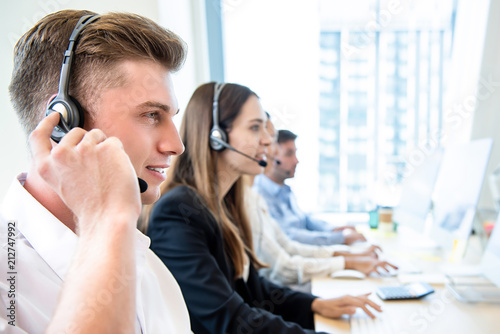 Fotomural Smiling friendly man working in call center office with team