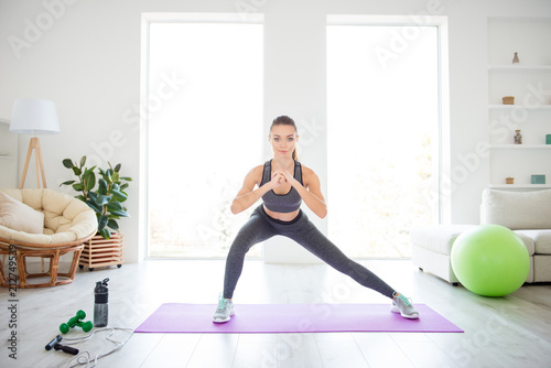 Fototapeta Equipment green fitness ball group trainer coach student people person concept. Let's go! Clasp your hands like this! Photo portrait of beautiful strong sportive lady doing squats on purple mat obraz