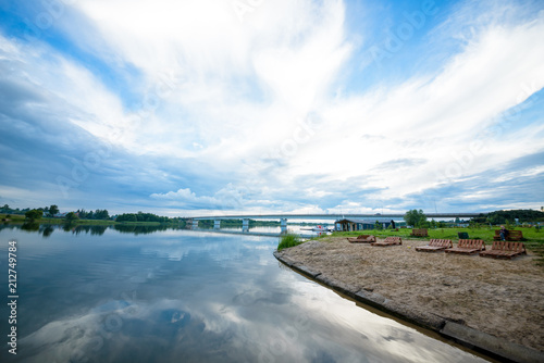 Poster Gris view of the river from the shore with a beautiful sky and clouds