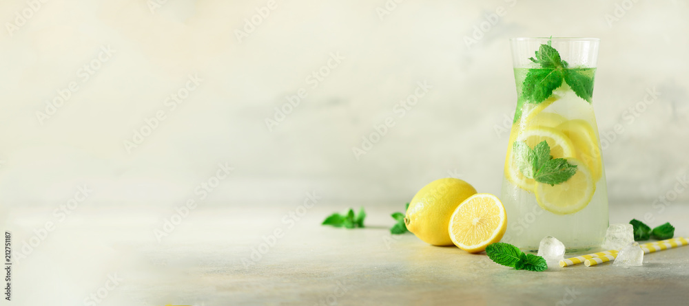 Fototapeta Detox water with mint, lemon on grey background. Banner with copy space. Citrus lemonade. Summer fruit infused water. Refreshing homemade cocktail, selective focus.