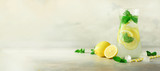 Detox water with mint, lemon on grey background. Banner with copy space. Citrus lemonade. Summer fruit infused water. Refreshing homemade cocktail, selective focus.