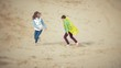 The mother plays with her son in a raincoat and runs down the sea at the beach