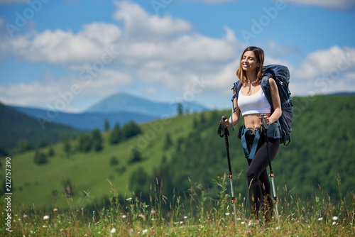 Happy sporty woman hiker with backpack and trekking sticks, enjoying summer day with closed eyes in the mountains Fototapet