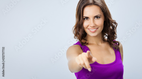 Spoed Foto op Canvas Wanddecoratie met eigen foto Woman pointing at something or pressing virual button, over grey