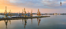 Golden Sunset Over Sea Port At Summer. Reflections Of Port Facilities And Beautiful Sky In Mirror – Like Calm Water