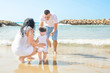 Young Parents Hold Support Cute Little Baby Toddler Girl Daughter Learning to Walk. Beach Blue Sea Sunlight. Authentic Atmosphere Candid Shot with Real People. Lifestyle Image. Togetherness Unity