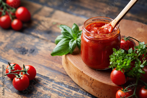 Fototapeta Tomato sauce in a glass jar, tomatoes and herbs on its side. obraz