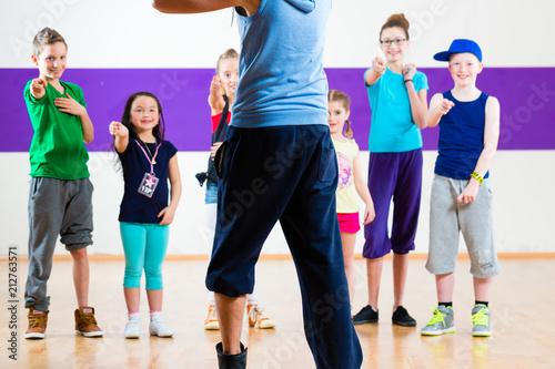 Fototapeten Tanzschule Dance teacher giving children fitness class in gym