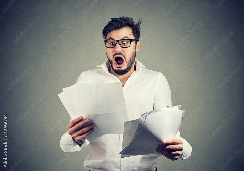 Fototapety, obrazy: Shocked business man looking through papers with bills