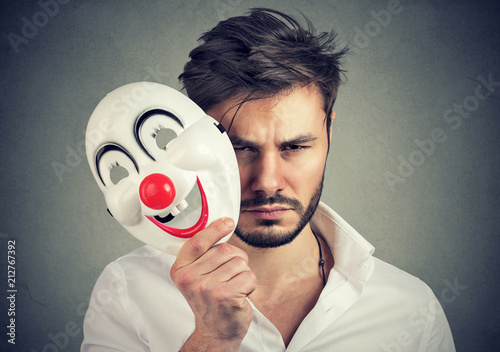Obraz Unhappy man covering feelings with mask - fototapety do salonu