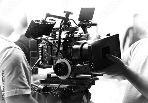 Valokuva  Movie shooting or video filming production by crew team and professional equipment such as super ultra high definition digital camera with tripod and lighting set in studio and black and white styles
