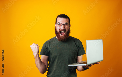 Fotografiet  Winner bearded man wearing glasses and looking at the camera holding his notebook and making a winner gesture