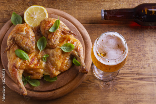 Foto op Plexiglas Bier / Cider Glass and bottle of beer and spatchcock chicken. Well-baked and juicy chicken is good food to glass of ale. Beer and meat. View from above, top studio shot