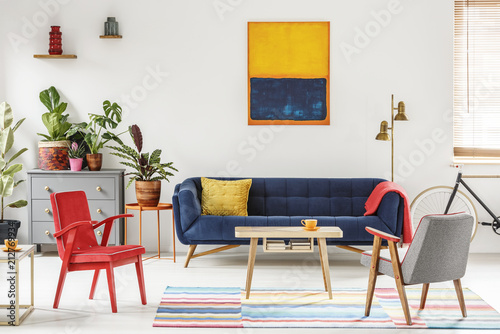 Deurstickers Wanddecoratie met eigen foto Red armchair next to wooden table and blue sofa in living room interior with painting. Real photo