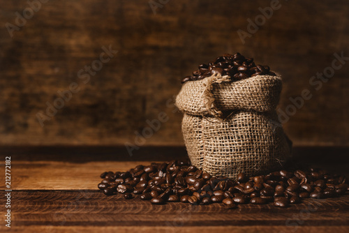Fotografie, Obraz  bunch of fresh roasted coffee beans with burlap sack on a wooden table
