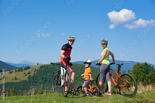 Young happy family tourists bikers, mom, dad and child resting with bicycles on grassy hill, looking in camera. Mountains view and blue sky on background. Healthy lifestyle and relations concept.