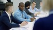 Team of multiethnic professionals sitting at meeting table and listening to presentation of colleague: mid-aged blonde businesswoman raising arm and asking a question