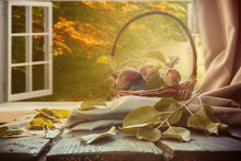 Apples In A Basket, A Plaid Book, A Cup On The Table Near A Window Overlooking The Autumn Landscape, Autumn Still Life, The Concept Of Coziness In A Rural House During Harvesting