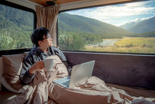 Young Asian Man Drinking Hot Coffee Working With Laptop Computer On The Bed In Camper Van With Mountain Scenic View Through The Window, Digital Nomad On Road Trip Concept