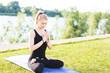 Beautiful young blonde girl doing yoga outdoors