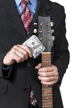 Businessman Holding A Bundle Of Dollars Near The Strings Of A Guitar, Close-up